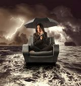 business woman on an armchair lost in the sea during a storm