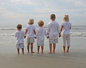 stock photo of holding hands  - five children holding hands looking out at the water at the beach - JPG