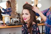 Professional female hairdresser making hairstyle to cheerful young woman with long hair poster