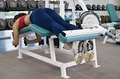 stock photo of hamstring  - A female lies on a hamstring curl machine in a gym - JPG