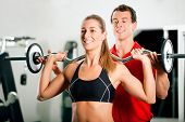 Woman in gym with personal fitness trainer exercising power gymnastics with a barbell