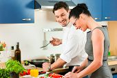 Young couple cooking - man and woman in their kitchen at home preparing vegetables for salad and pas