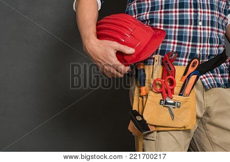 poster of Closeup of hardhat held by construction worker on grey background. Bricklayer holding red helmet and