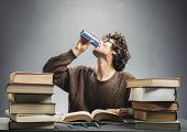 Young man drinking energy drink while studying. College student concept. Energizing before learning. poster