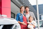 Mother, father, and child buying car at dealership, a new family auto poster