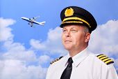 Photo of an airline pilot wearing the four bar Captains epaulettes, shot against a sky background wi