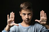 Little boy with words Stop bullying on his hands against black background poster