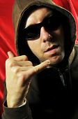 stock photo of gangsta  - Gangsta like man wearing sunglasses is gesturing the call sign - JPG