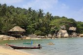 stock photo of southeast asian  - longtail boat on beach in front of resort built into the rock formations and jungle of koh tao in the gulf of thailand - JPG