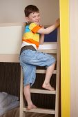stock photo of bunk-bed  - Smiling little boy going up the ladder of bunk bed - JPG