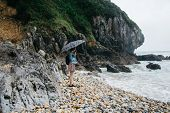 Portrait of young woman with umbrella walking on the beach in overcast weather. Rocky coastline of t poster