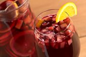 foto of sangria  - Refreshing red wine punch called sangria mixed with orange apple mango pieces served in wine glass garnished with orange slice on the rim  - JPG