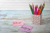 Notes with text Stop bullying and pencil holder on table poster