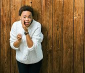 Beautiful young african american woman wearing sweater over isolated background hand on mouth tellin poster