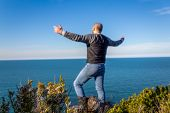 Bald Man On A Cliff Edge, Spread His Arms Against Sea View. Happy And Confident   Man On The Cliff W poster