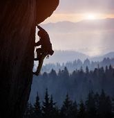 Silhouette Of Man Rock Climbing On Straight Vertical Rock At Sunrise. Sunlight Covering Mountains On poster