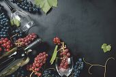 Bottle, Two Wine Glasses, Fresh Grapes And Leaves On Black Background. Flat Lay, Top View, Copy Spac poster