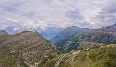 A High Alpine Mountain Valley And Mountain Road Pass. The Road Passes Through High Mountain Peaks An poster