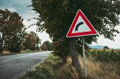 Image - Illuminated European Traffic Sign (red Triangle) -curved Road, Green Meadow And Field On Bac poster