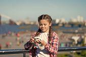 Girl Little Kid Hold Foldable Headphones While Walk Outdoors. Modern Music Gadget. Benefits Of Folda poster