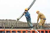 stock photo of formwork  - builder worker with tube from truck mounted concrete pump pouring cement into formwork reinforcement - JPG