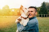 Man have fun with his dog Labrador in park at sunset poster