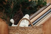 Rustic Basket With Fir Branches,festive Wrapping Paper, Cozy Gloves And Hat On Rustic Wooden Backgro poster