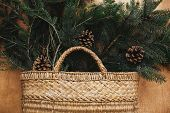 Rustic Basket With Fir Branches And Cones On Rustic Wooden Background. Flat Lay. Winter Holiday Prep poster