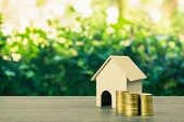 Property Investment, Home Loan, Reverse Mortgage Concept. A Small House Model With Stack Of Gold Coi poster