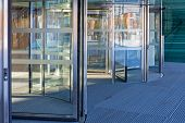 Automatic Revolving Doors At Modern Building Entrance poster