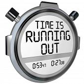 stock photo of stopwatch  - A stopwatch or timer with the words Time is Running Out to warn you that the clock is ticking and the deadline or finish point is near and you should hurry or speed up to complete the game or job - JPG
