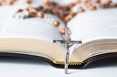 stock photo of leather-bound  - Cross of rosary beads resting against open bible - JPG