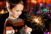 Young boy holding burning sparkler on festive lights background