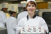 Happy female chef presenting plate of meringues smiling at the camera