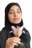 stock photo of hijabs  - Beautiful arab woman wearing a hijab smelling a flower isolated on a white background - JPG