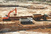 image of boom-truck  - loader excavator machine loading dumper truck at sand quarry - JPG