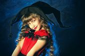 Pretty little girl in a costume of witch posing over dark background. Halloween.