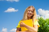 stock photo of 13 year old  - Happy blond 13 years old girl stand with with the yellow book in the park on bright sunny summer day - JPG
