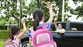 foto of bye  - little girls say good bye with father in front of school - JPG