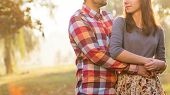 foto of jeans skirt  - Young couple in love walking in the autumn park holding hands looking in the sunset - JPG