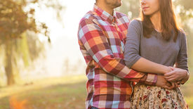 image of jeans skirt  - Young couple in love walking in the autumn park holding hands looking in the sunset - JPG
