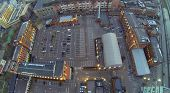 Cars on parking in courtyard among buildings at winter. Aerial view