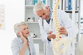 stock photo of vertebrae  - Male doctor explaining the spine to senior patient at medical office - JPG