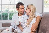 Relaxed loving young couple with coffee cups sitting on sofa at home