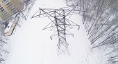 Big frosty power lines among winter snowy park near building. Aerial view