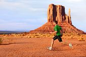 Running man sprinting in Monument Valley. Athlete runner cross country trail running outdoors in ama
