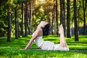 picture of prone  - Woman in white costume doing yoga on the green grass in the park around pine trees - JPG