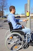 stock photo of zebra crossing  - Wheelchair user waiting on a pedestrian crossing