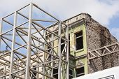stock photo of scaffold  - Scaffolding against an old abandoned building under renovation - JPG