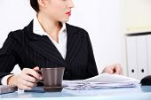 Working business woman with documents and a cup of coffee or tea.